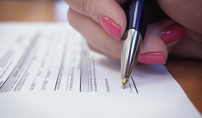 woman's hand holding pen about to sign a document